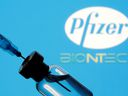 A vial and syringe are seen in front of a displayed Pfizer and Biontech logo in this illustration taken Jan. 11, 2021. The vaccine presents a